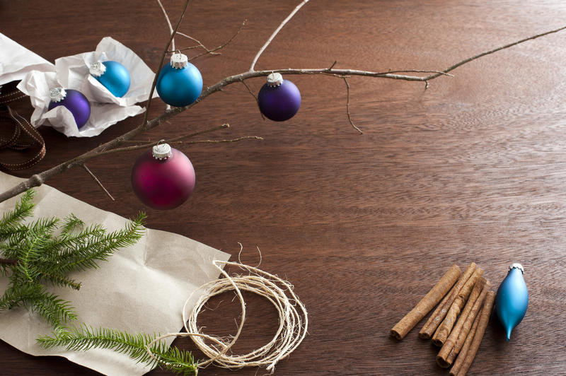 High Angle View of Bare Tree Branch on Textured Wooden Surface Scattered with Christmas Ornaments, Evergreen Sprigs, String and Cinnamon Sticks - Festive Still Life with Copy Space