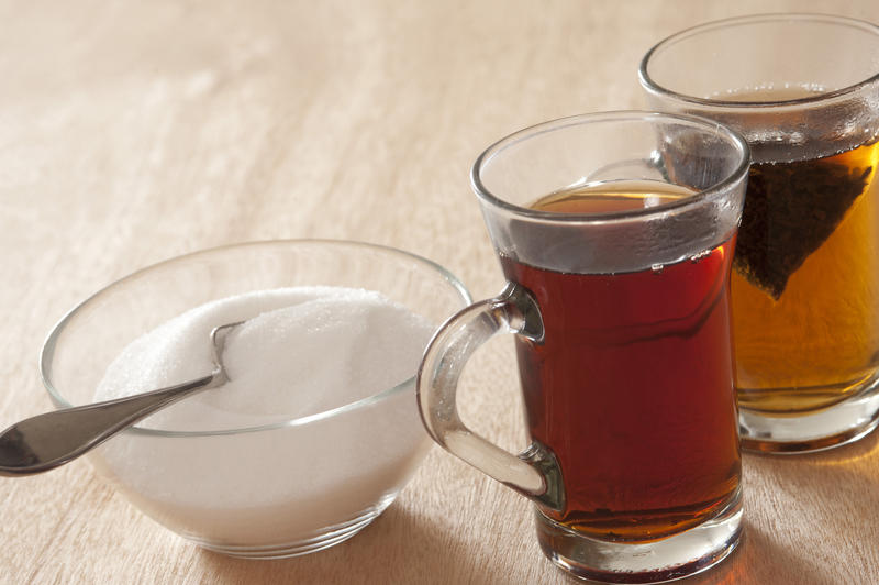 Two glass mugs of hot sweet black tea, one with a teabag still steeping, alongside a bowl of white sugar