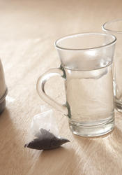 11601   Tea Bag on Wooden Table Next to Mug of Hot Water