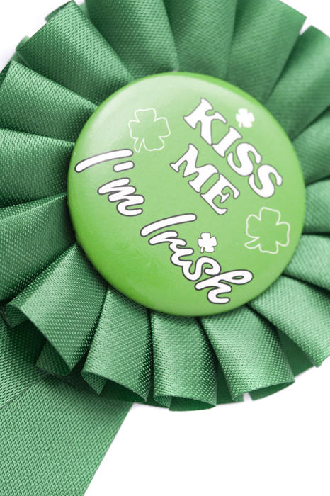 A novelty green ribbon rosette with a st patricks day message in the middle