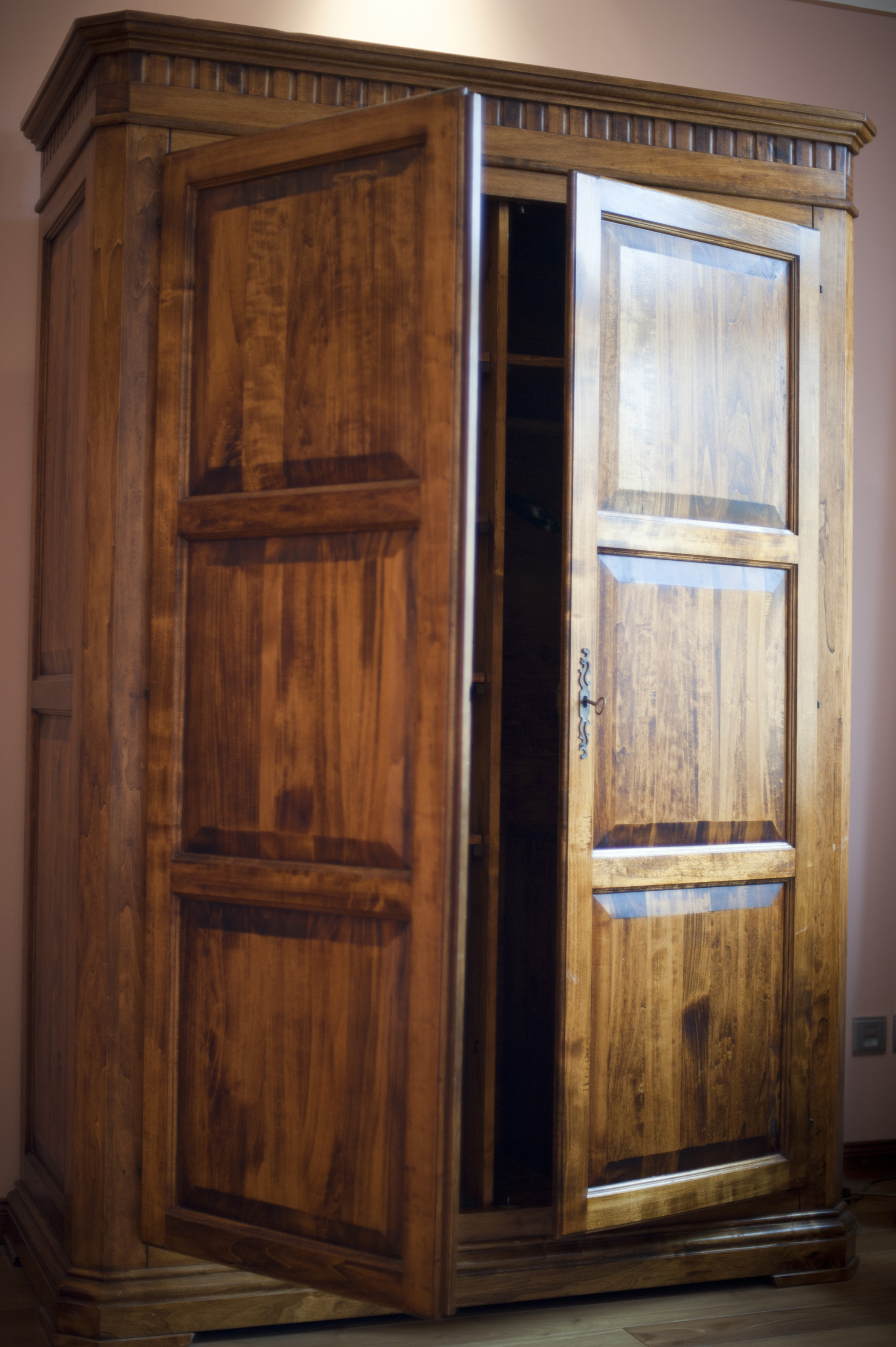 Rustic large wooden wardrobe or armoire with the doors ajar to reveal ...