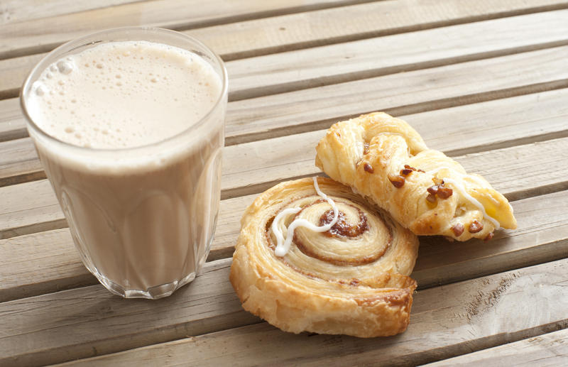 Latte snack with a glass of milky frothy coffee ad two Danish pastries on a slatted wooden table outdoors, close up high angle view