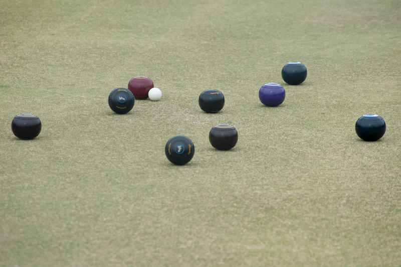 Bowling balls lying around a jack on a bowling green in a game of lawn bowls with copyspace below