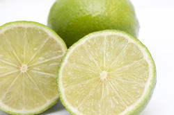 8423   Close up of two fresh nutritious limes, on white