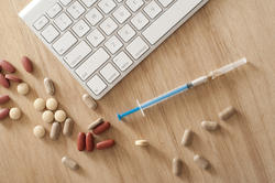 11551   Computer Keyboard and Syringe Surrounded by Pills