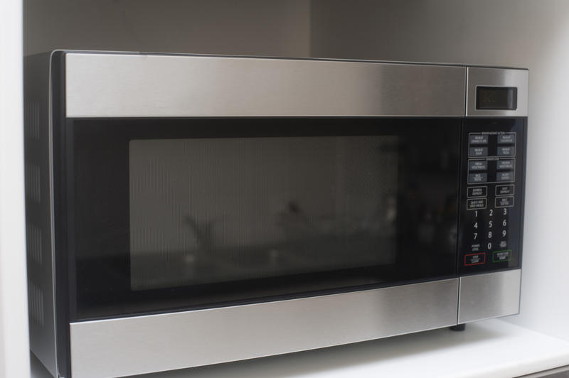 Large modern microwave with a glass door and electronic control panel installed in a kitchen unit