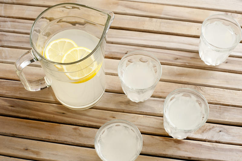 High Angle View of Pitcher of Freshly Squeezed Lemonade with Lemon Slices on Wooden Picnic Table Beside Four Glasses of Lemonade - Glasses of Refreshing Lemonade on Outdoor Table