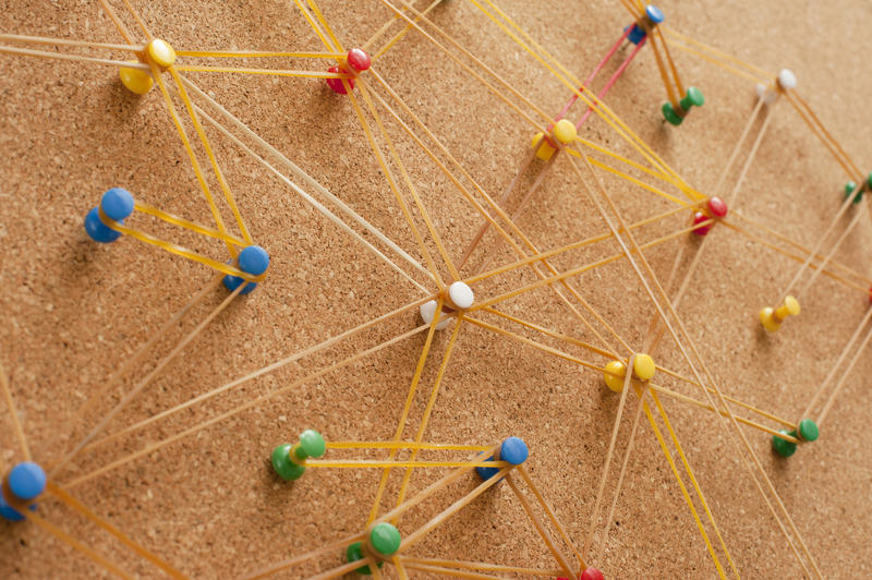 Network Concept Using Assorted Colored Pins on Cork Board Connected with Rubbers