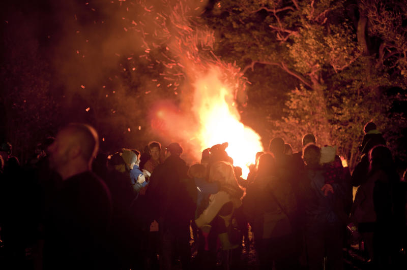 November 5th celebrations with a large crowd of people gathered around a bonfire in a field with trees commemorating Guy Fawkes or Bonfire Night - not model released