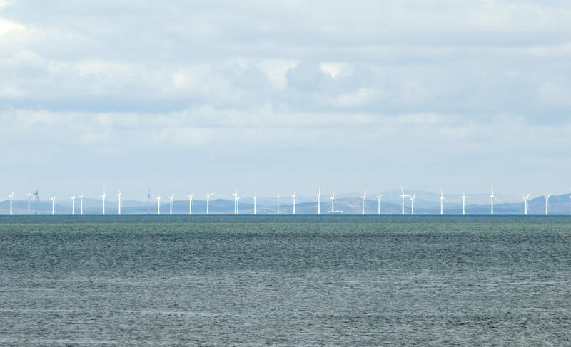 Offshore windfarm with a long row of wind turbines generating electricity from the kinetic energy of the wind near Whitehaven