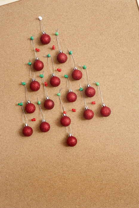 Office Christmas celebration with colorful red baubles formed into the shape of a Christmas tree on a cork noticeboard with copy-space - working Christmas