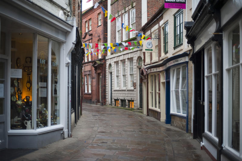 View of the narrow cobbled street and quaint old storefronts of Grape Lane in Whitby