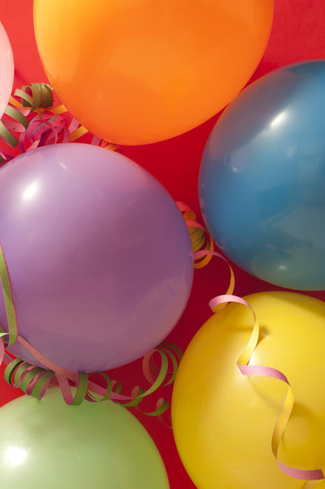 Close up Colored Birthday Party Balloons with Streamers Against Red ...