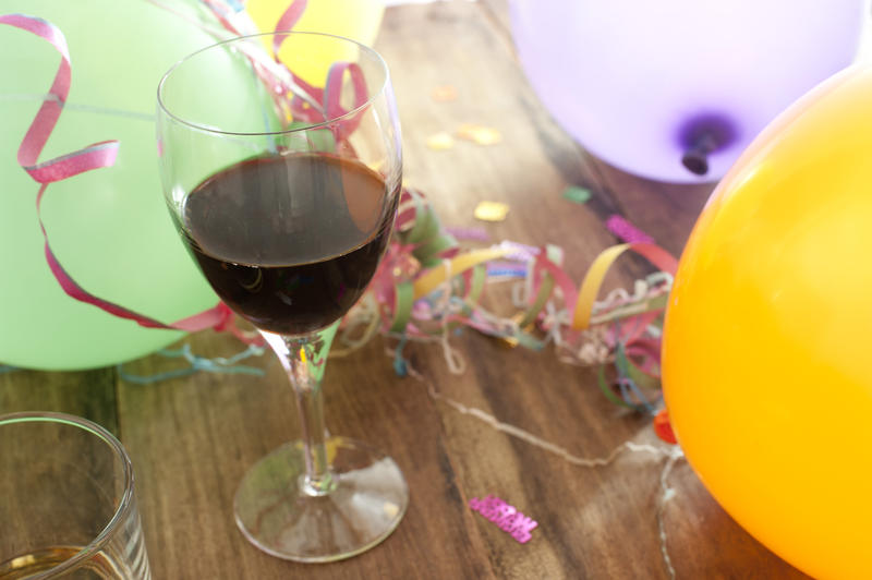 Party background of colorful balloons and streamers with a glass of red wine in the foreground on a wooden table