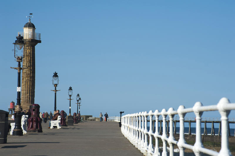View along the West Pier at Whitby showing people walking on the promenade with the navigation lighthouse at the end
