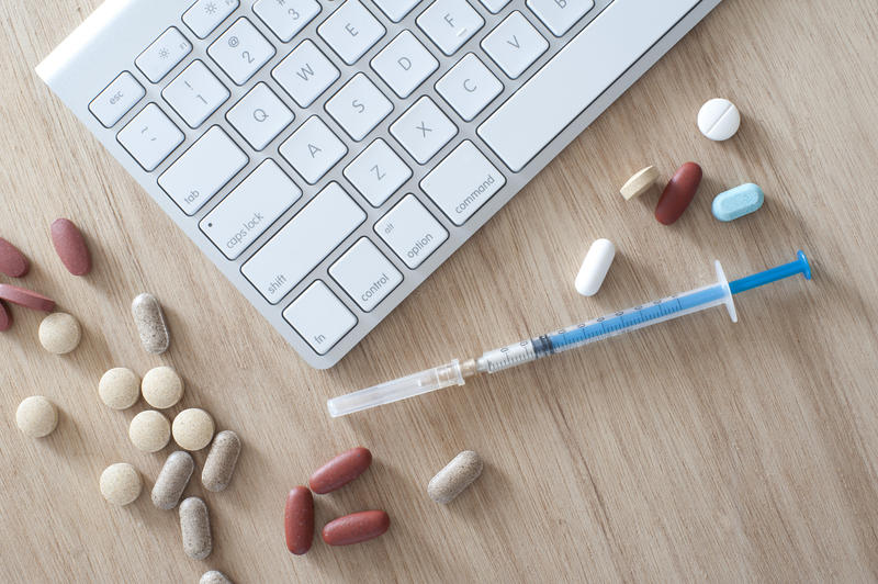 Online medicine and healthcare concept with an overhead view of a computer keyboard on a wooden desk with assorted pills and tablets and a disposable injection needle and syringe