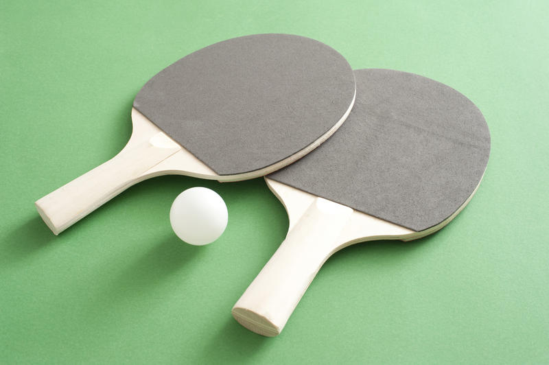 Two new table tennis bats and a ball lying on the green wooden table used to play the game