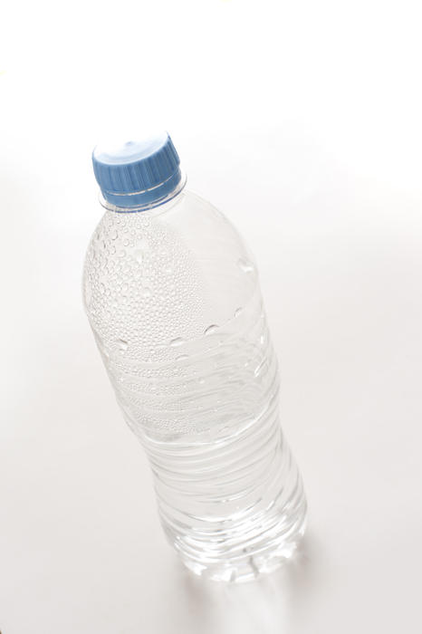 Empty unlabeled plastic water bottle with droplets still adhering to the sides in a healthy drinking and recycling concept