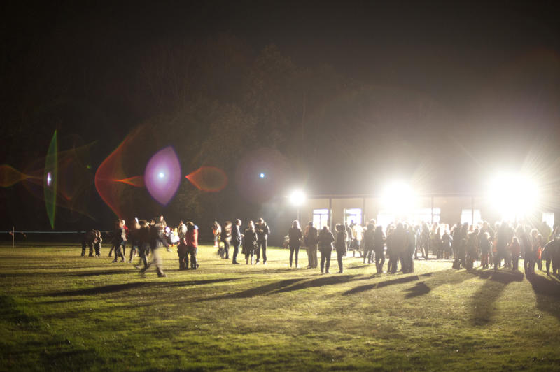 Crowd of people gathering on a sports field illuminated by bright spotlights as they prepare to celebrate Bonfire Night on 5th November