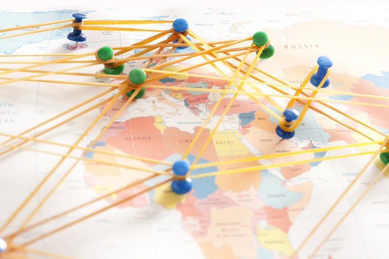 Conceptual Image of Push Pins Inserted in Various Locations on World Map Connected with Rubber Bands