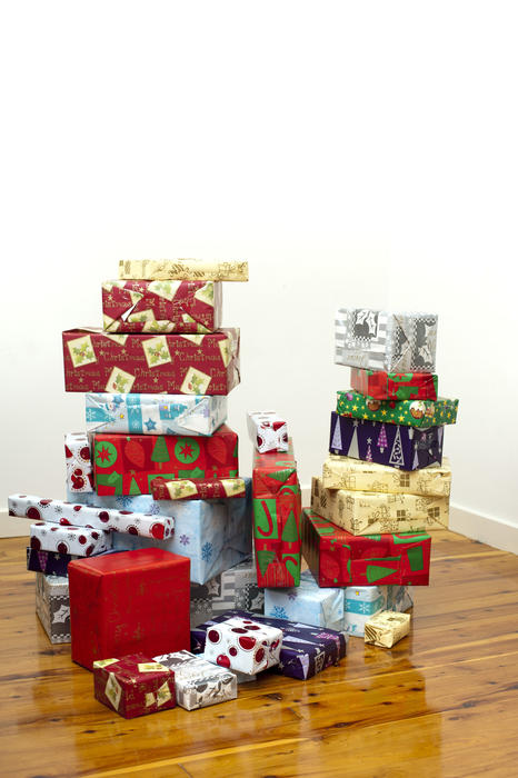 Stack of colourful Xmas presents and packages in traditional patterned seasonal gift wrap paper on a hardwood floor with a white wall background with copyspace