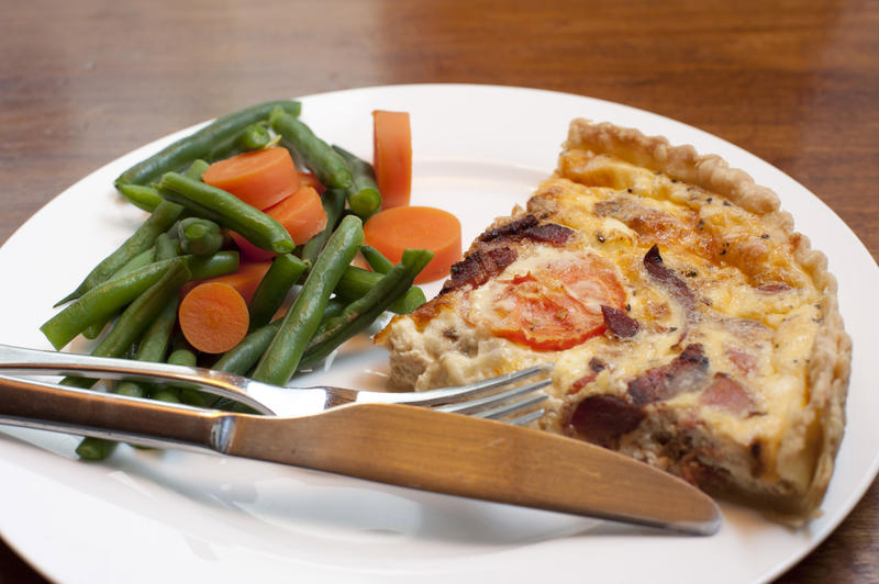 Slice of savoury quiche with a crispy crust served with cooked fresh green beans and carrots for a healthy light meal or snack