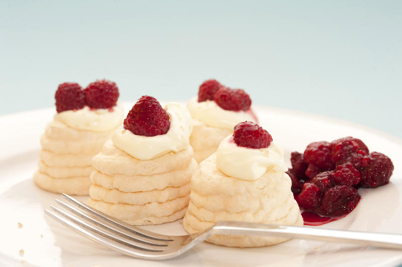 Serving on a plate of mini meringue pavlovas with decorative twirled cases filled with whipped cream and raspberries