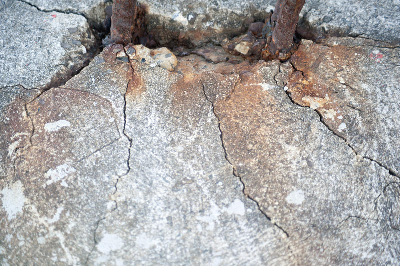 Close Up of Two Rusted Rebar Mounted in Cracked Cement of Structure with Rust Stains