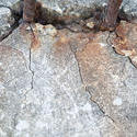 10930   Close Up of Rusted Rebar Mounted in Cracked Cement