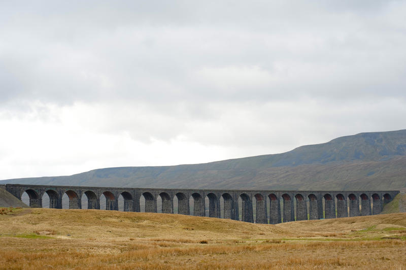 Panoramic view of the stone arches of the Ribblehead Viaduct, a curved stone Victorian railway viaduct crossing the River Ribble in North Yorkshire