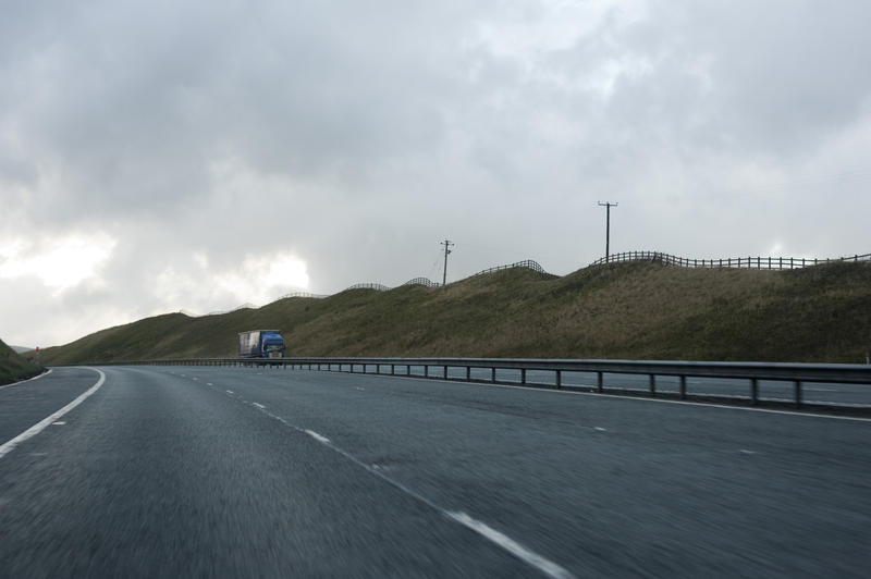 No Traffic on a long long road, with Rails at the Middle, Grassy Hills on the Side Under a Stormy Sky