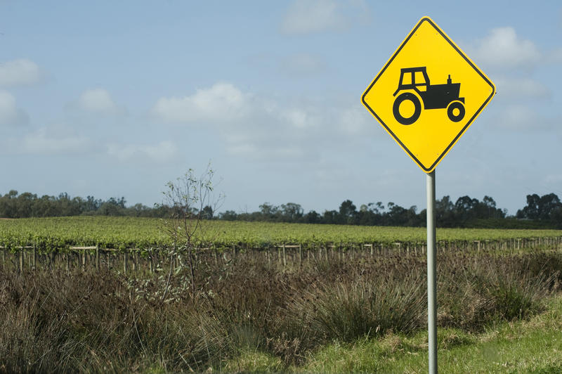 Yellow traffic warning sign for agricultural vehicles and equipment showing the silhouette of a tractor at the roadside alongside an agricultural field