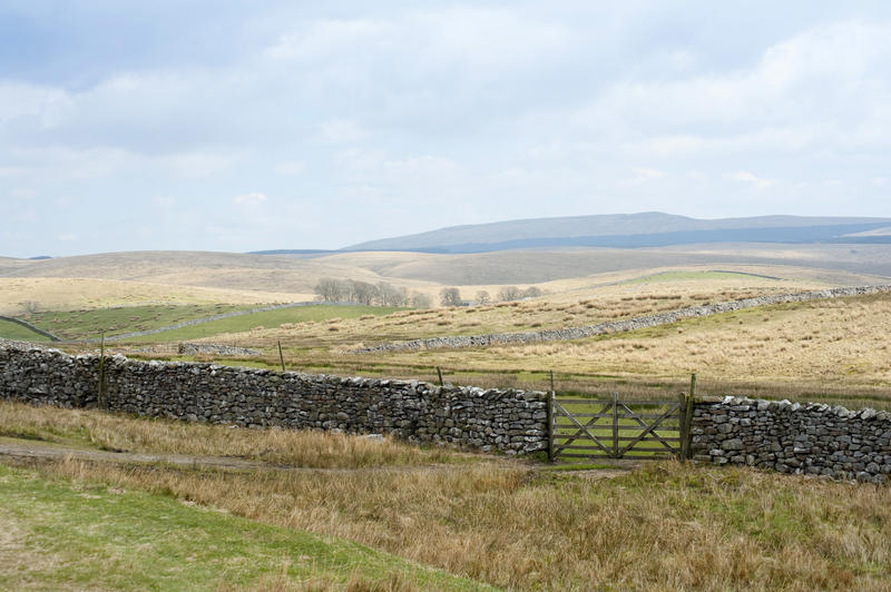 Rural English landscape with rolling gentle hills and a farm gate set in a dry-stone wall in the foreground