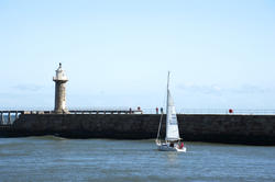 8026   j92 Yacht sailing past Whitby breakwaters