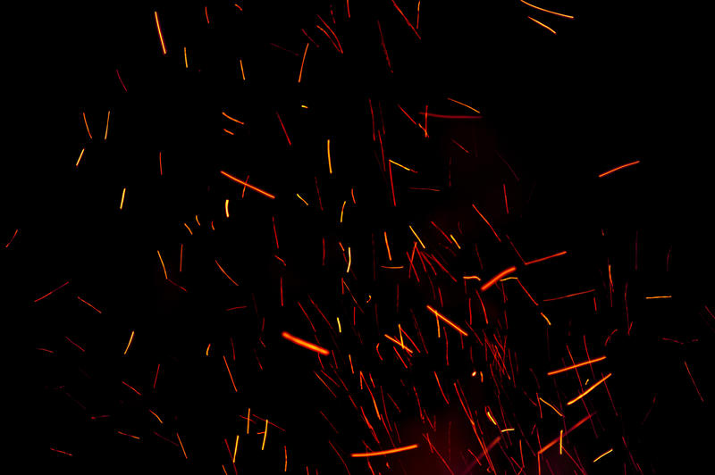 Background of fiery burning embers leaving an abstract pattern of motion colorful orange trails in the darkness above a bonfire or campfire