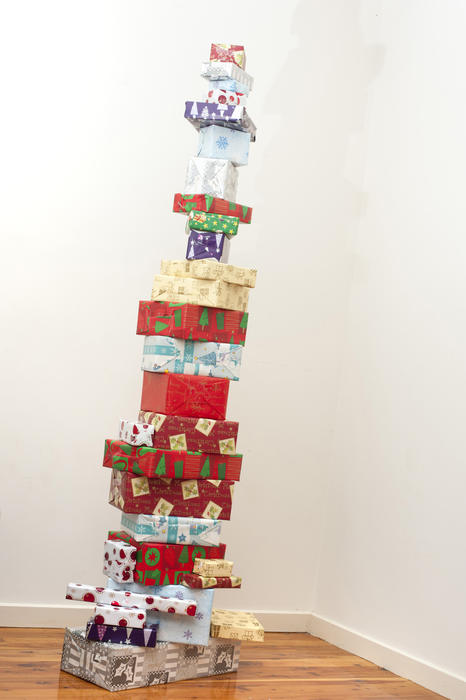 Tall stacked tower of Christmas gifts making a unique colourful decoration in the corner of a room