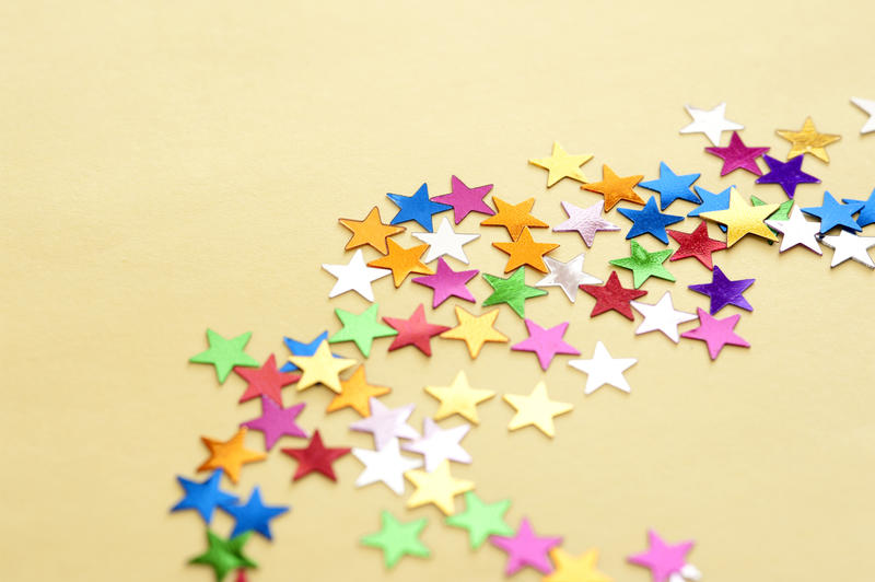 Colorful Star Shaped Stickers Scattered in Starburst Trail on Yellow Background with Copy Space