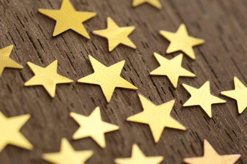 Close up shot of golden stars on wooden background