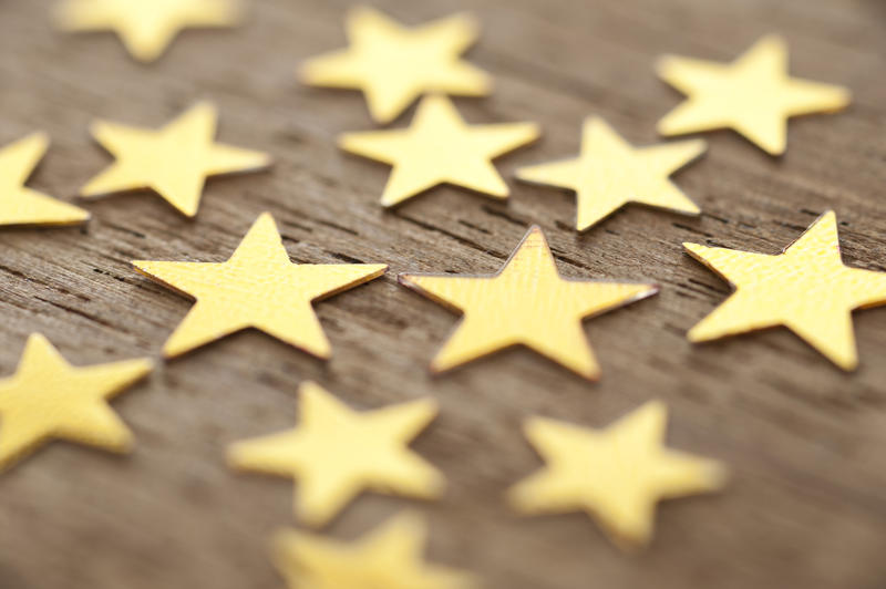 Close Up of Gold Stars Scattered on Wooden Surface, Full Frame Background with Shallow Depth of Field