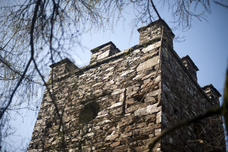 External facade of a stone folly with a crenellated tower viewed low angle against a sunny blue sky