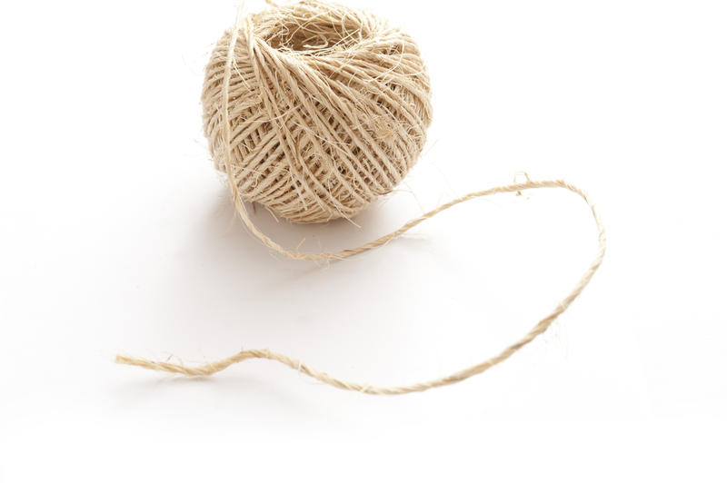Ball of household string or twine from twisted natural hemp fibers on white