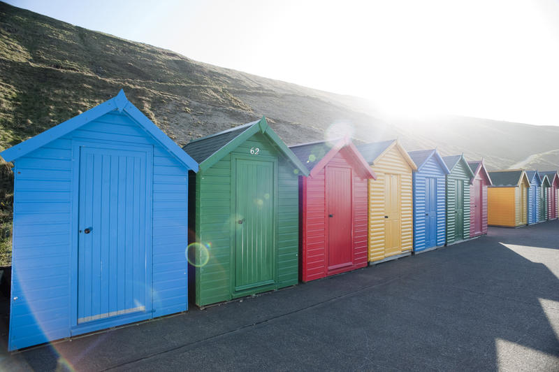 Row of brightly coloured wooden beach huts on Whitby West Cliff under a hot sun for changing when bathing