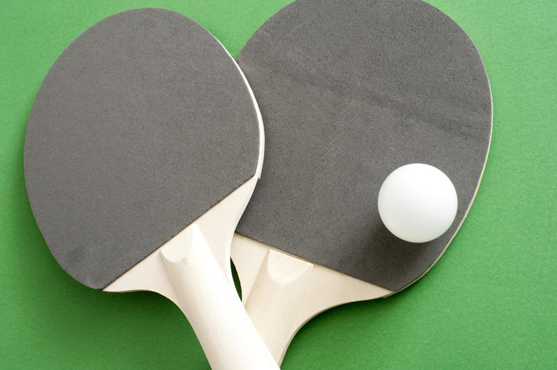 Close up Gray and White Rackets with One White Ball for Table Tennis Sports, Isolated on Green Background.