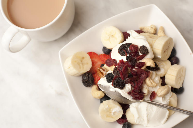 Tea and healthy breakfast cereal topped with yoghurt , raisins and sliced fresh strawberry and bananas, high angle view