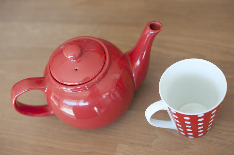 Close up Glossy Red Teapot and an empty cup for One Cup on Top of a Wooden Table