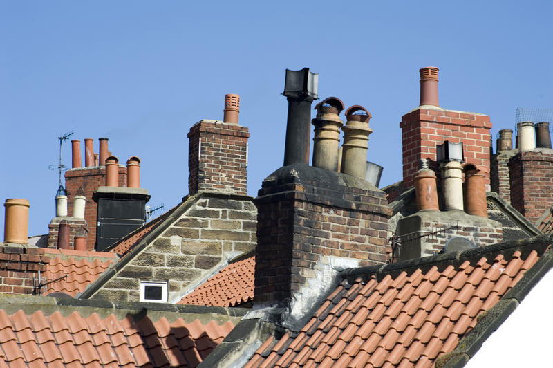 A view across tiled rooftops showing the roof details with chimney stacks and pots