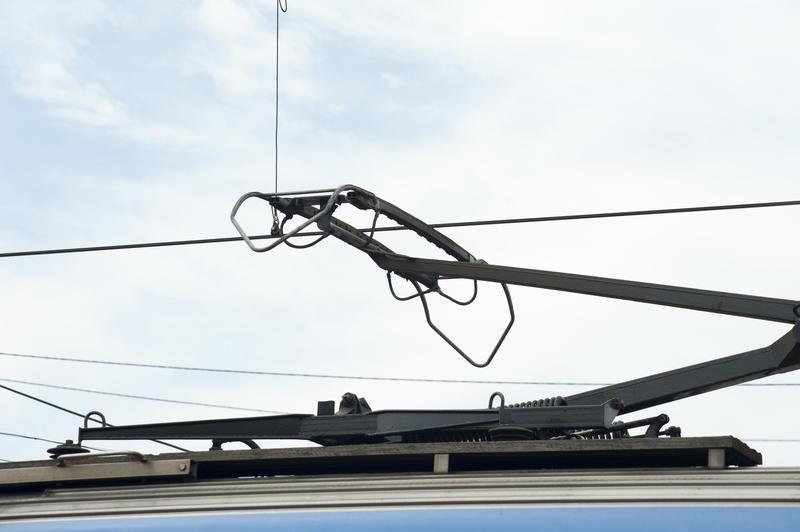Pantograph on top of a train connected to overhead power lines, close up detail