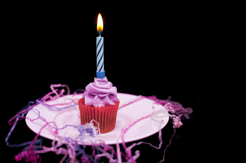 a small cup cake with pink icind, a candle and paink and blue celebration streamers