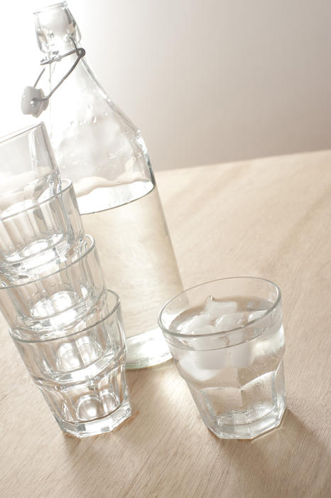 A glass bottle with still water and tumblers on a wooden table