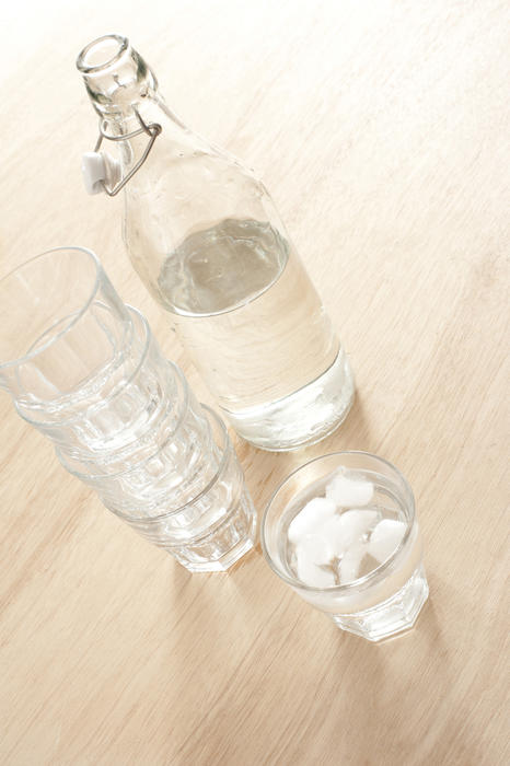 Open bottle of water and several glasses, one with water and ice cubes on wooden table